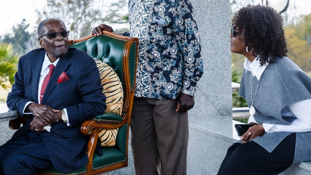 "Zimbabwe's former President Robert Mugabe speaks with his wife Grace Mugabe during a press conference held at his ""Blue Roof"" residence in Harare."