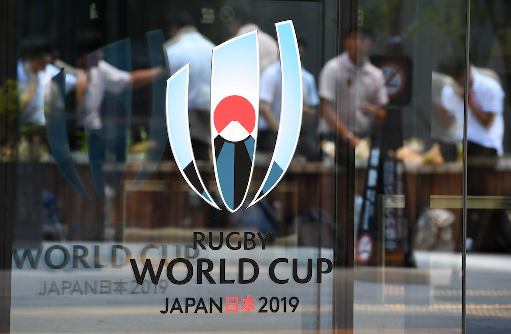 People are reflected of the logo of the Rugby World Cup 2019 in Tokyo.