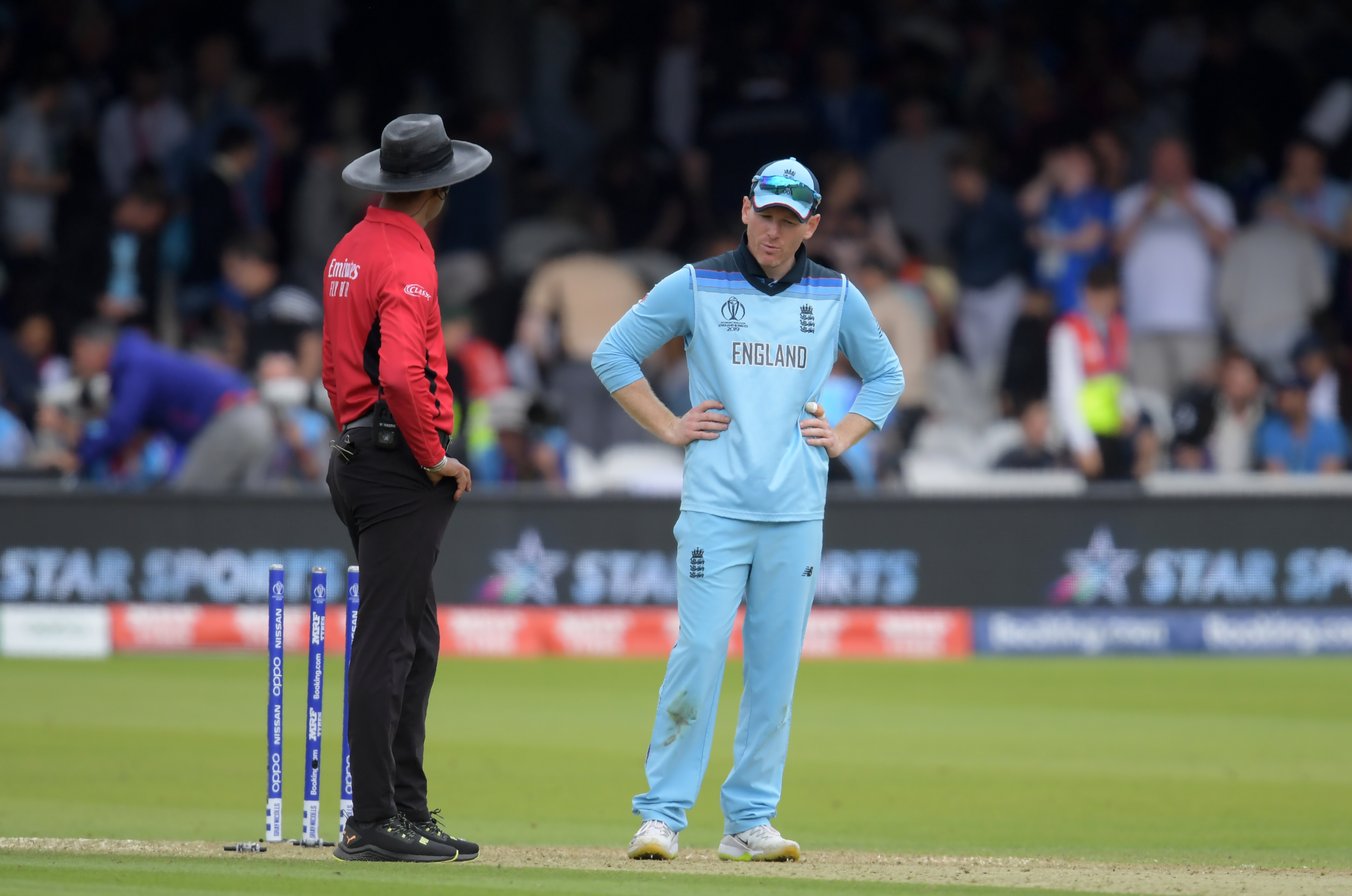 England's captain Eoin Morgan (R) speaks with umpire Kumar Dharmasena as he looks at the wicket after the New Zealand innings during the 2019 Cricket World Cup final between England and New Zealand at Lord's Cricket Ground in London on July 14, 2019.
