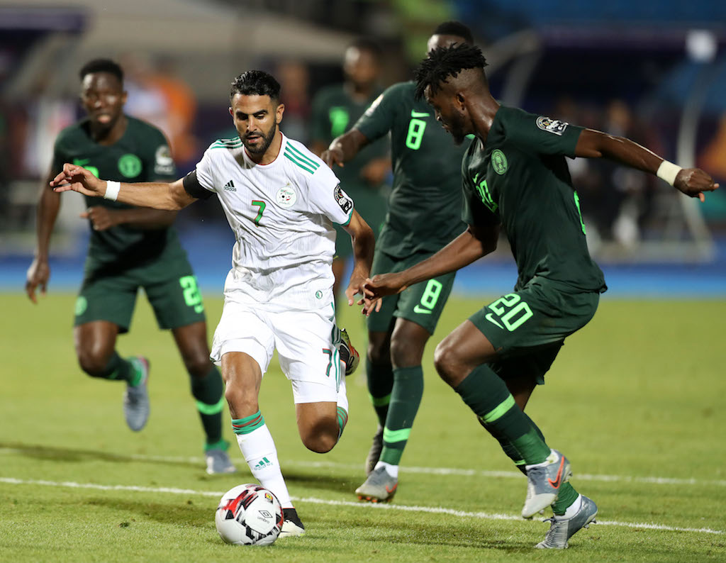 Riyad Mahrez of Algeria tackled by Josiah Kenneth Omeruo, Peter Etebo and Collins Awaziem of Nigeria during the 2019 Africa Cup of Nations Finals semifinals match at Cairo International Stadium, Cairo, Egypt on 14 July 2019.