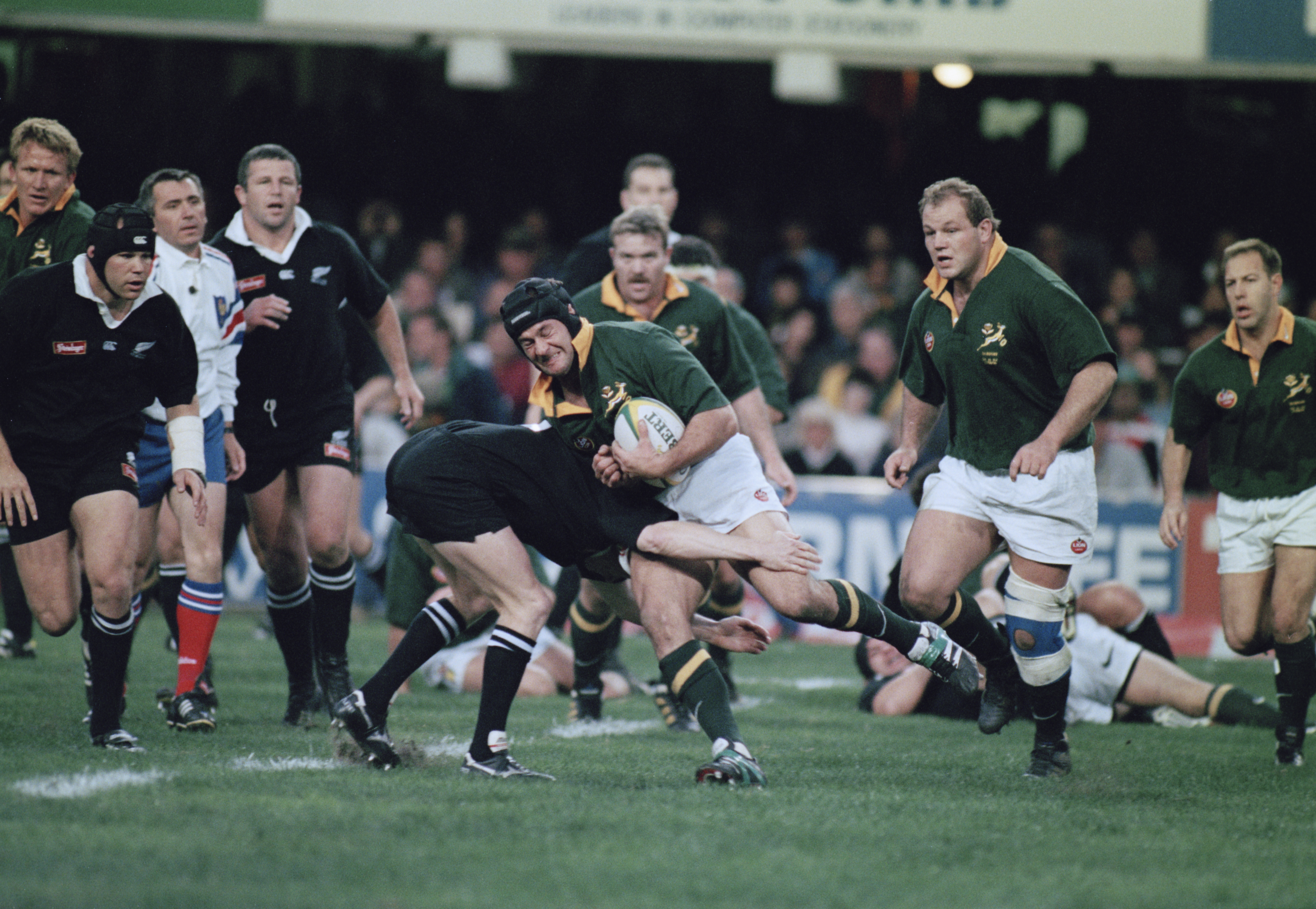 File: South African rugby player Ruben Kruger (1970 - 2010, centre) is tackled during an international against New Zealand, Durban, 17th August 1996. New Zealand won the match 23-19.