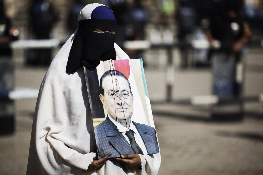 A fully-veiled Muslim Egyptian woman who supports former president Hosni Mubarak (portrait) waits for the verdict to be announced outside the Cairo court.