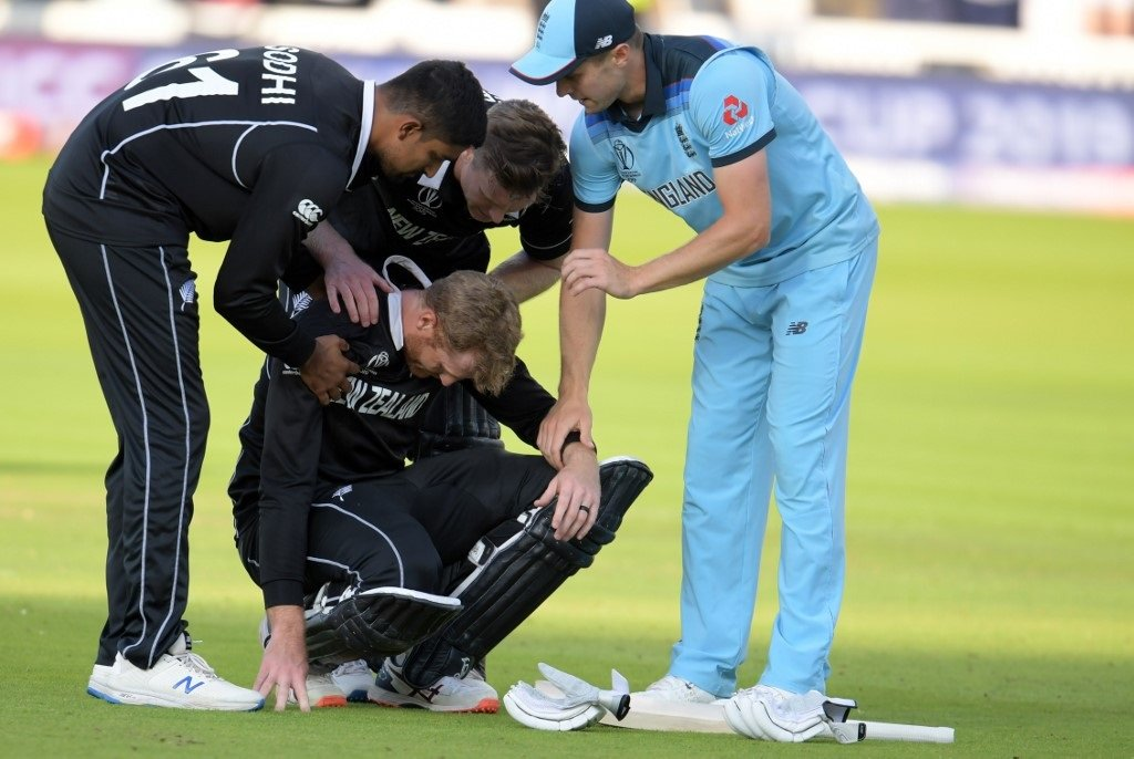 New Zealand's Martin Guptill (C) is assisted by teammates and England's Chris Woakes (R) after the 2019 Cricket World Cup final between England and New Zealand at Lord's Cricket Ground in London on July 14, 2019.