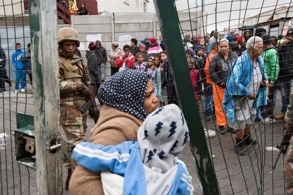 A woman carries a child through a broken gate as members of the South African National Defense Force (SANDF) patrol in the streets of Hanover Park, among inhabitants, on July 18, 2019.