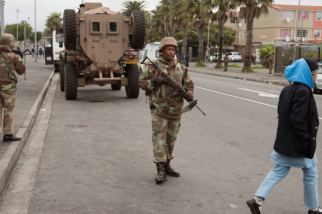 Members of the South African National Defense Force(SANDF) patrol a street in Manenberg in Cape Town.