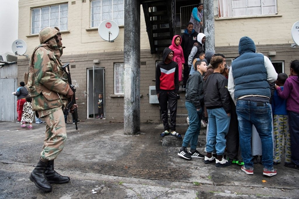 A member of the South African National Defense Force (SANDF) approaches a group of people as he patrols in the streets of Hanover Park on July 18, 2019.