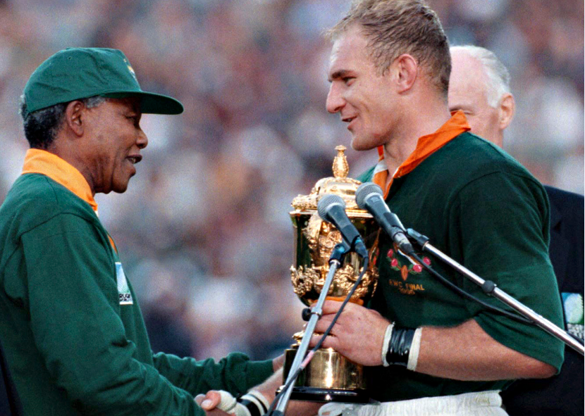 South African president Nelson Mandela, dressed in a No 6 Springbok jersey, congratulates the Springbok captain Francois Pienaar after South Africa beat the All Blacks by 15-12 to win the 1995 Rugby World Cup.