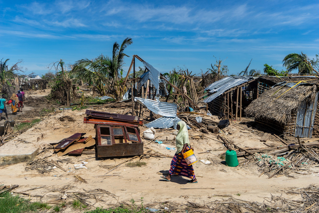 A woman walks past destroyed houses on her way to an aid distribution centre in Mozambique's Cabo Delgado province in the aftermath of a devastating cyclone.