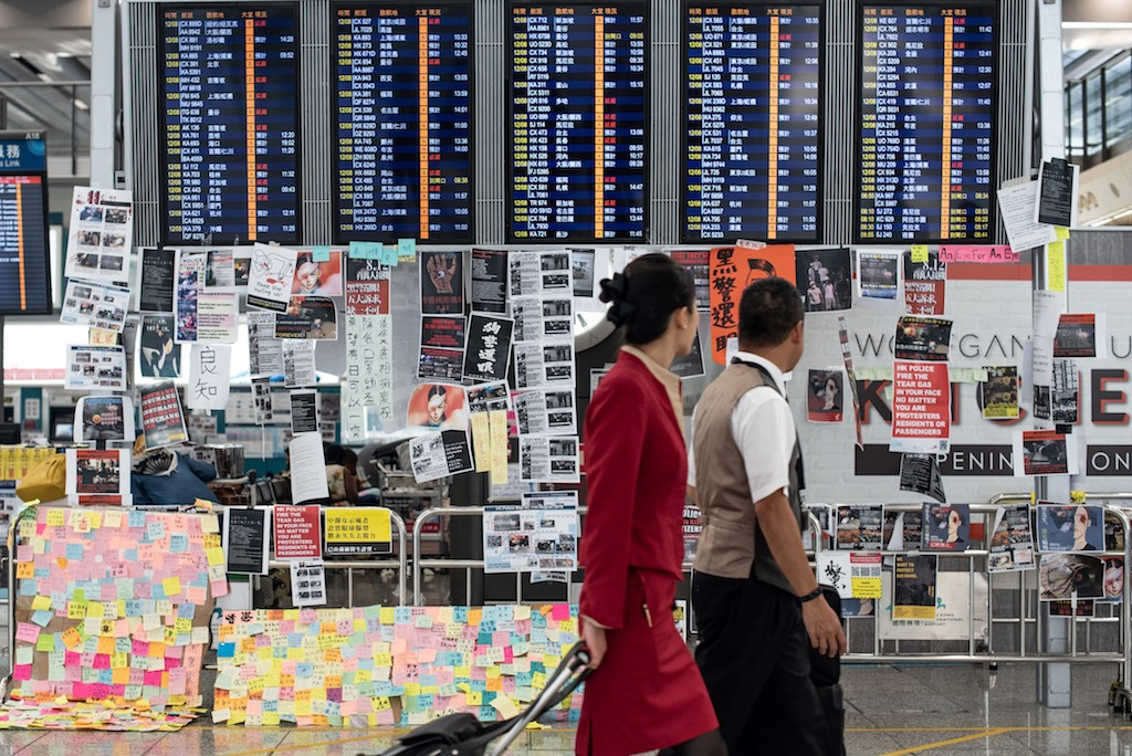 Two flight attendants walk past an electric display board covered with memos and posters at Hong Kong's international airport.