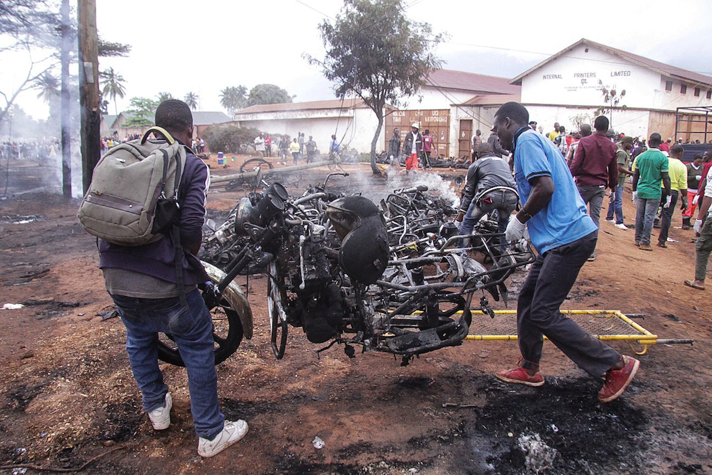 Two men carry the remains of a burnt out motorbike after a fuel tanker exploded in Morogoro.