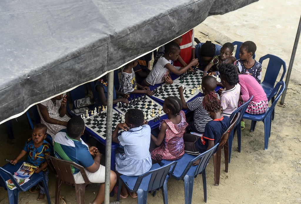 Children sit under a canopy as they play during a chess class at Ogolonto in Ikorodu district of Lagos on 17 August 2019.