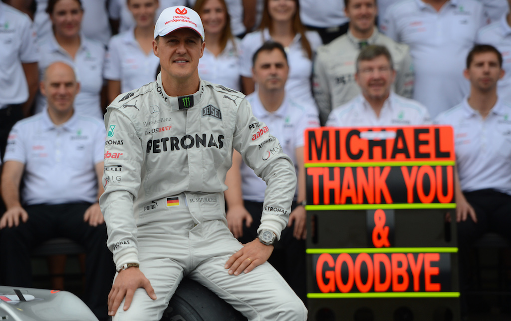 Michael Schumacher poses with the Mercedes team in the pits on November 25, 2012 at the Interlagos speedway in Sao Paulo, Brazil.