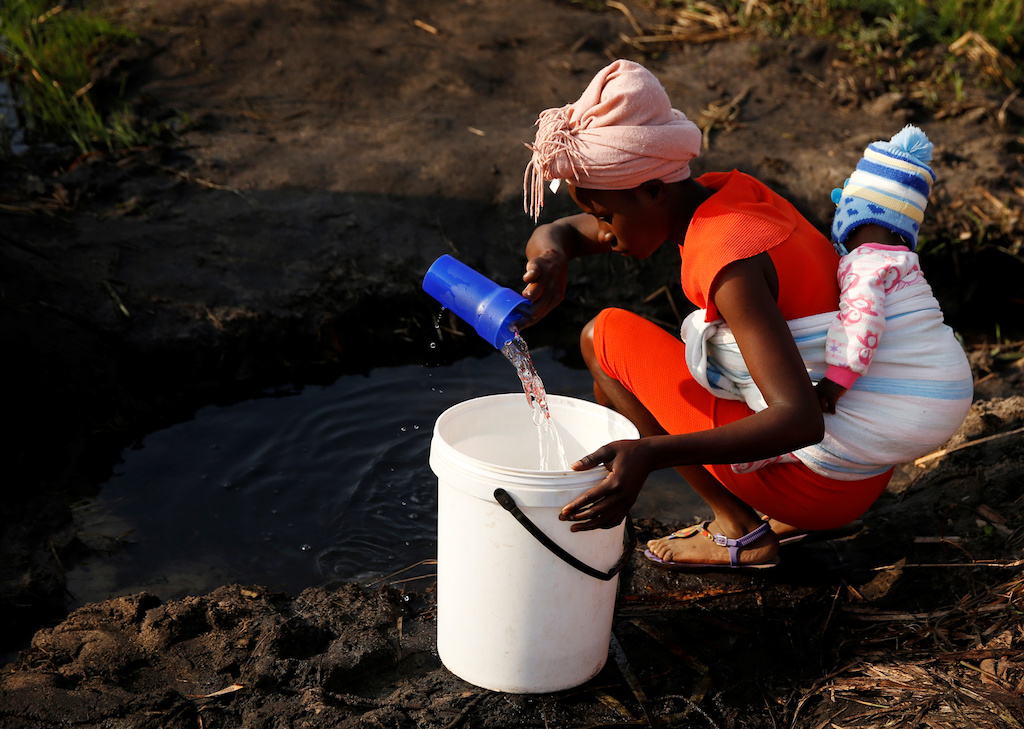 A women with a baby on her back collects water in Mabvuku, a highly-populated suburb in Harare, Zimbabwe, 3 September 2019.