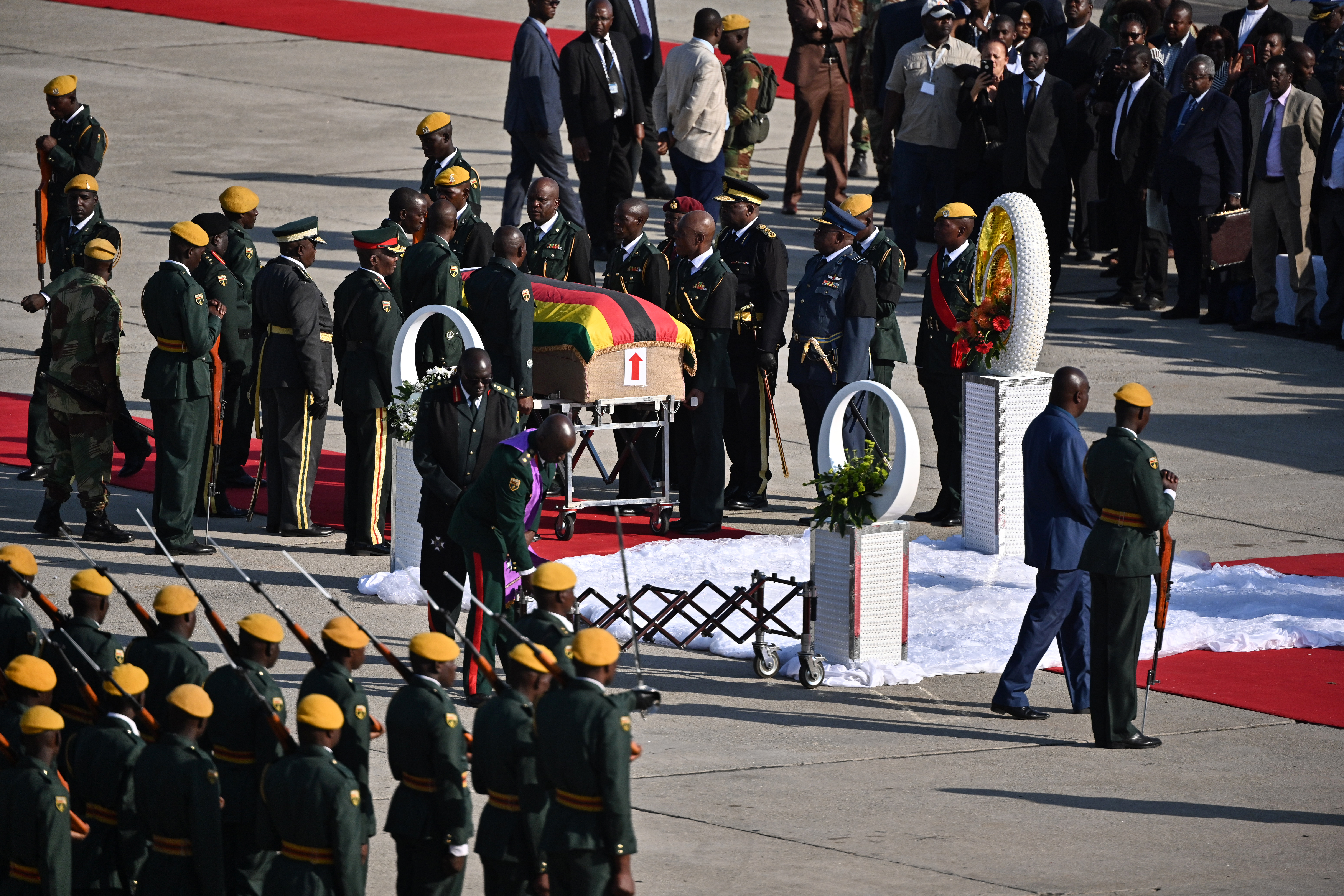 Pall bearers stand by the casket of late Zimbabwean President Robert Mugabe as its arrives in Harare on September 11, 2019.