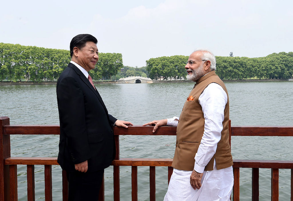 India's Prime Minister Narendra Modi (R) and Chinese President Xi Jinping looking on along the East Lake.