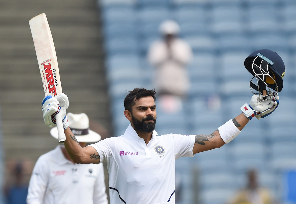 India's cricket team captain Virat Kohli celebrates after scoring a century (100 runs) on the second day of the second Test cricket match between India and South Africa at Maharashtra Cricket Association Stadium in Pune on October 11, 2019.