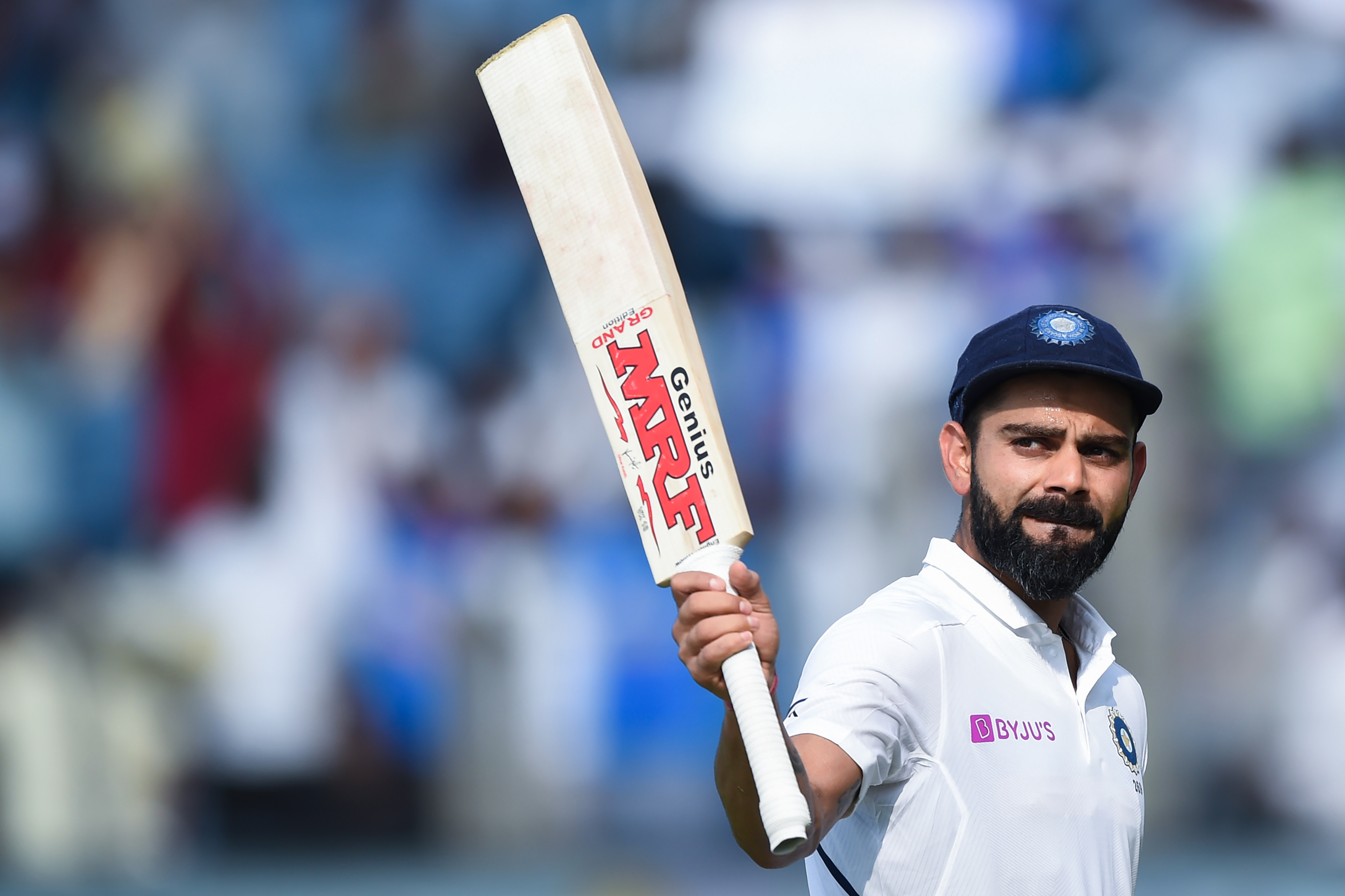 India's cricket team captain Virat Kohli rises his bat as he leaves the field after declearing their first innings during the second day of the second Test cricket match between India and South Africa at Maharashtra Cricket Association Stadium in Pune on October 11, 2019.