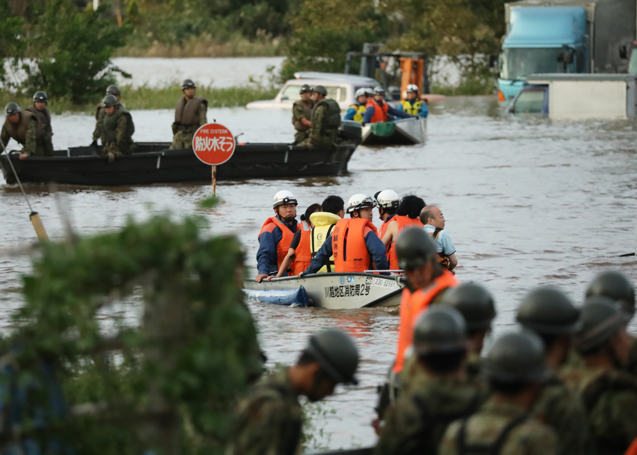 Fire department workers (C) evacuate residents from a flooded area in Kawagoe, Saitama prefecture on October 13, 2019, one day after Typhoon Hagibis swept through central and eastern Japan.