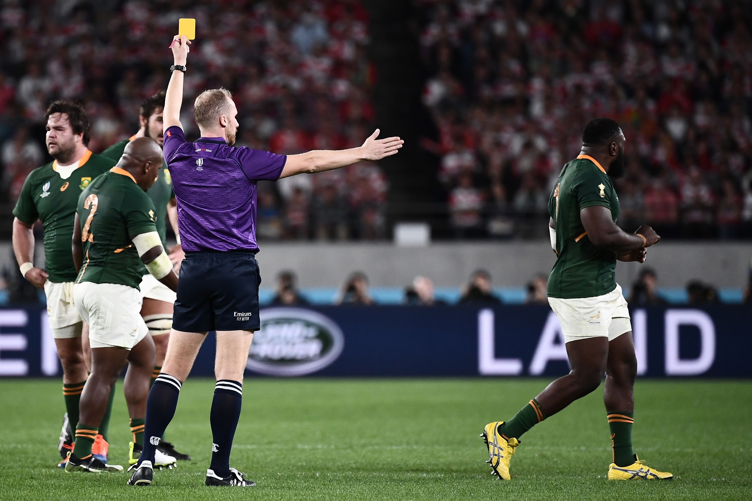 South Africa's prop Tendai Mtawarira (R) receives a yellow card from English referee Wayne Barnes (L) during the Japan 2019 Rugby World Cup quarter-final match between Japan and South Africa.