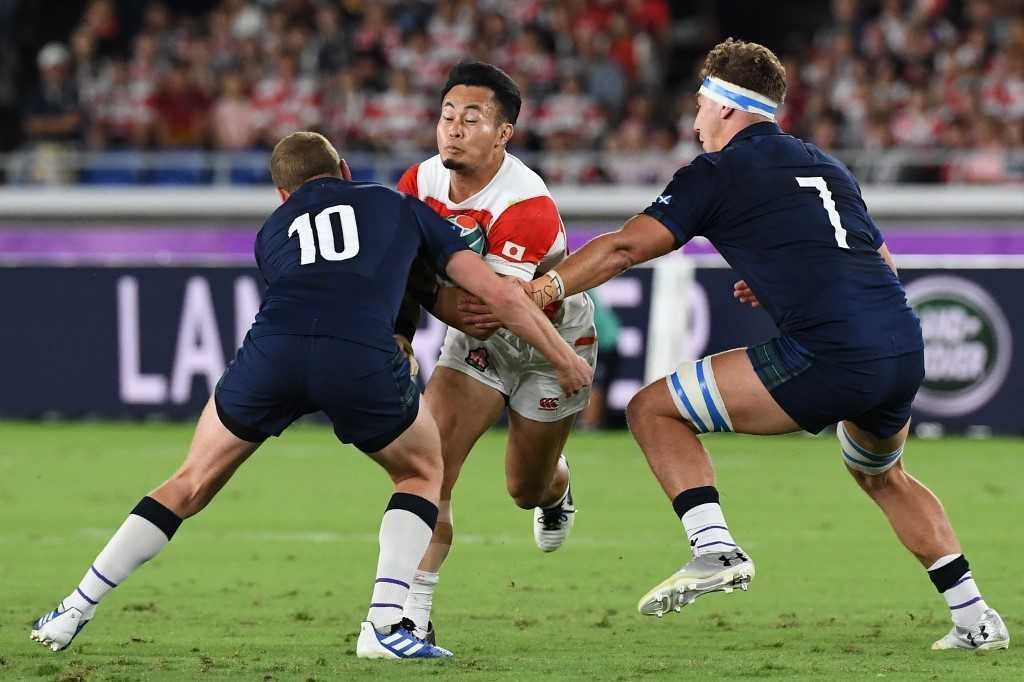 Scotland's fly-half Finn Russell (L) and flanker Jamie Ritchie (R) tackle Japan's wing Kenki Fukuoka during the Japan 2019 Rugby World Cup Pool A match.