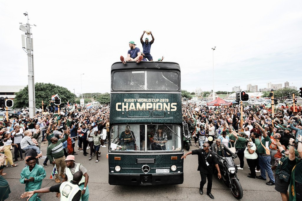 Springbok supporters celebrate while the South African Rugby World Cup winner team parades through the Durban CBD on an open top bus in Durban on November 8, 2019.