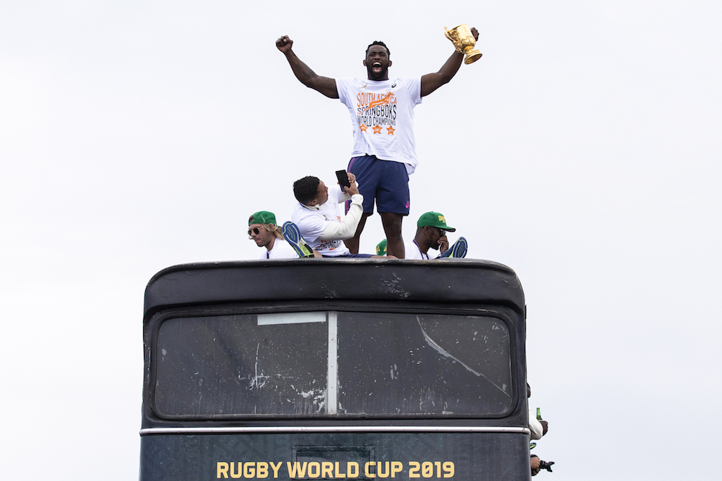 Captain Siya Kolisi (C) celebrates and holds up the Web Ellis Trophy as the South African Rugby World Cup winner team parades on an open top bus.