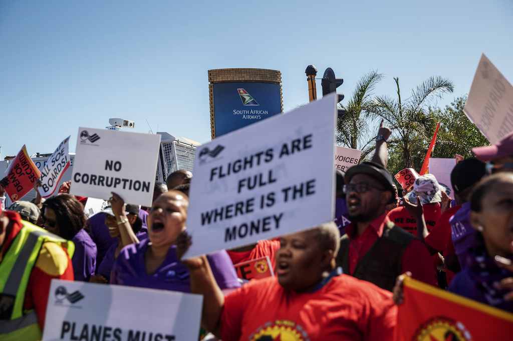 SAA workers and union members sing and dance during a picket protest outside the OR Tambo International Airport in Johannesburg.