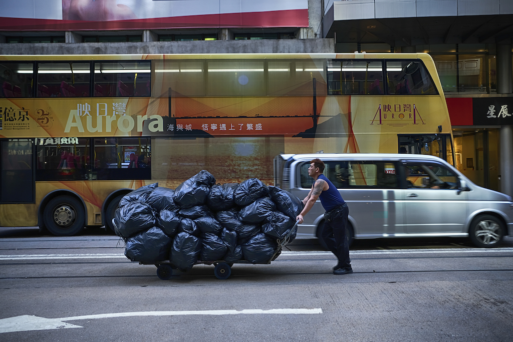 A man pushes a cart loaded with rubbish bags along a road in Hong Kong on December 6, 2019.