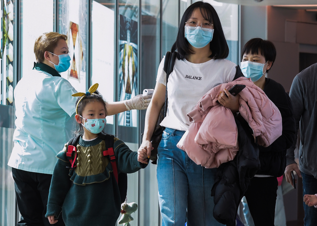 A health officer (L) screens arriving passengers from China at Changi International airport in Singapore as authorities increased measure against coronavirus.