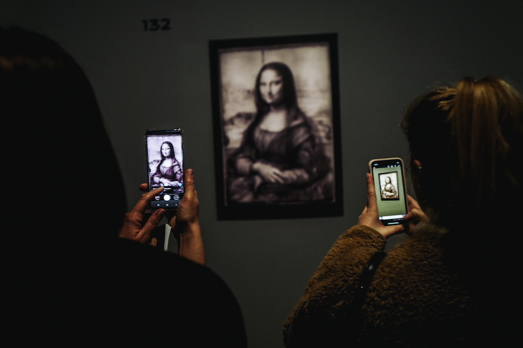 Visitors take photos of a version of the painting 'Mona Lisa' at the 'Leonardo da Vinci' exhibition at The Louvre Museum.