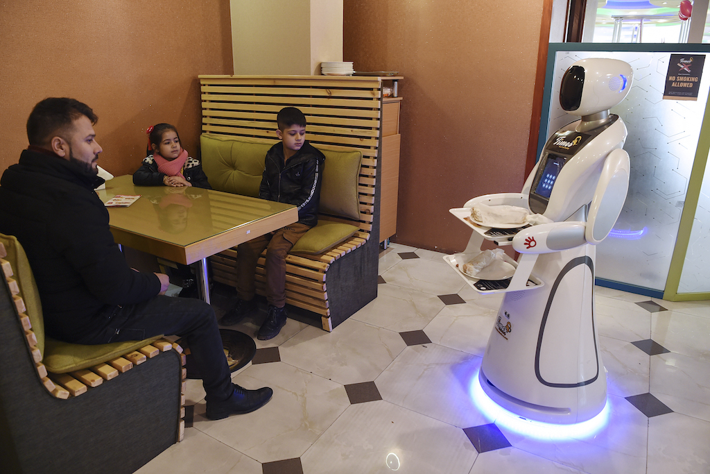 A waitress robot named Timea delivers food to customers at a Times Fast Food restaurant in Kabul.