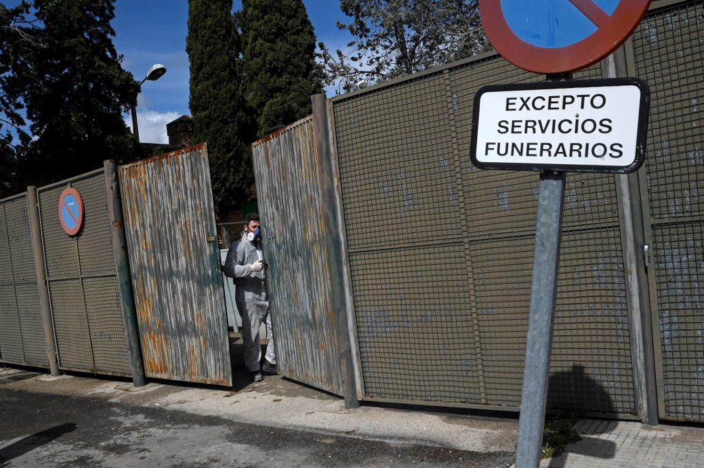A worker in a protective suit opens the gate for an approaching hearse outside the crematorium of La Almudena cemetery in Madrid on March 24, 2020