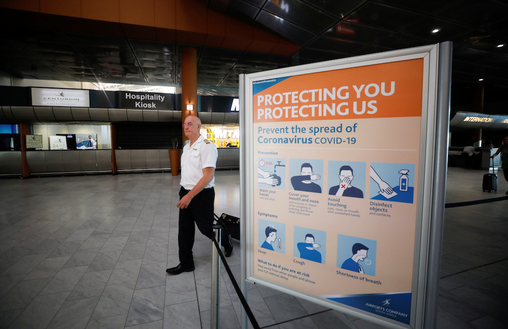 A cabin crew member walks past a sign informing travellers about the coronavirus disease (COVID-19), at the Cape Town International Airport, in Cape Town,SouthAfrica.