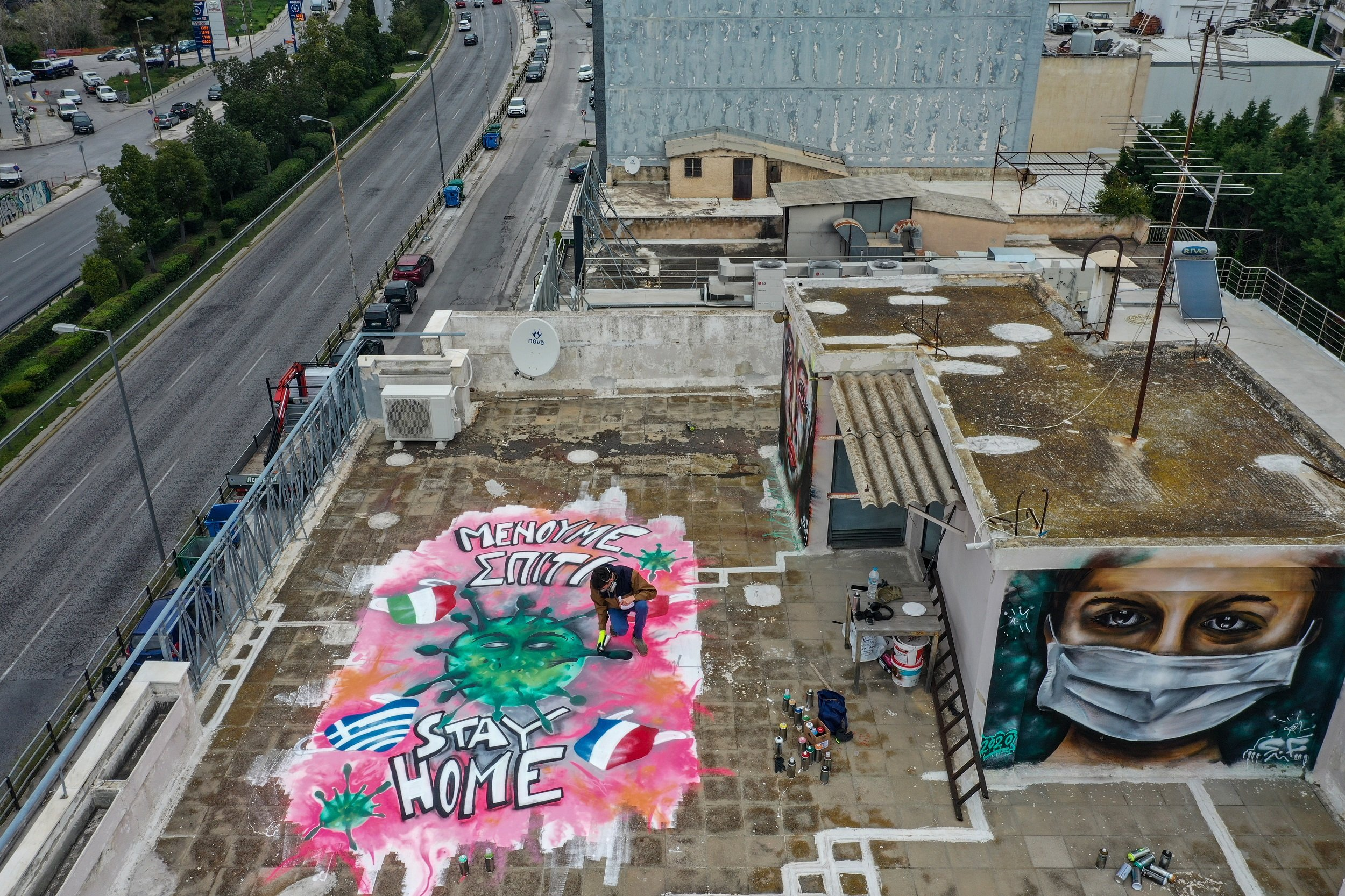 On the roof of his building, a Greek artist displays graffiti urging people to stay home and to wear a mask.