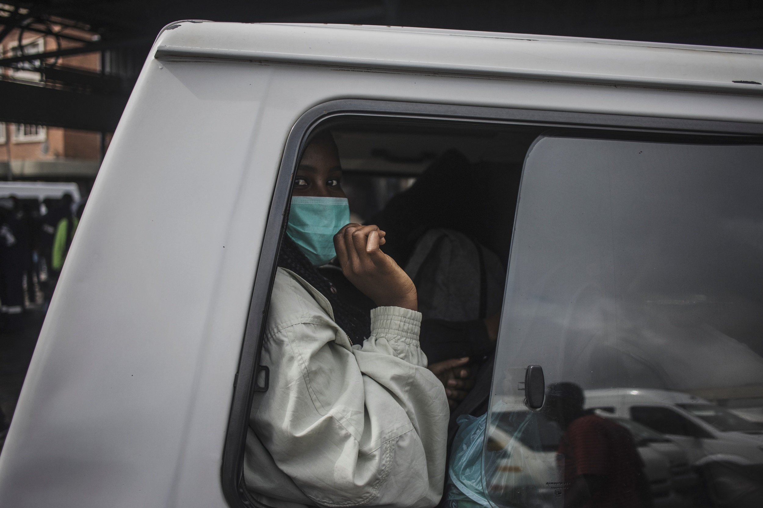 A commuter wearing a face mask as a preventive measure sits in a taxi at the Wanderers taxi rank in Johannesburg.