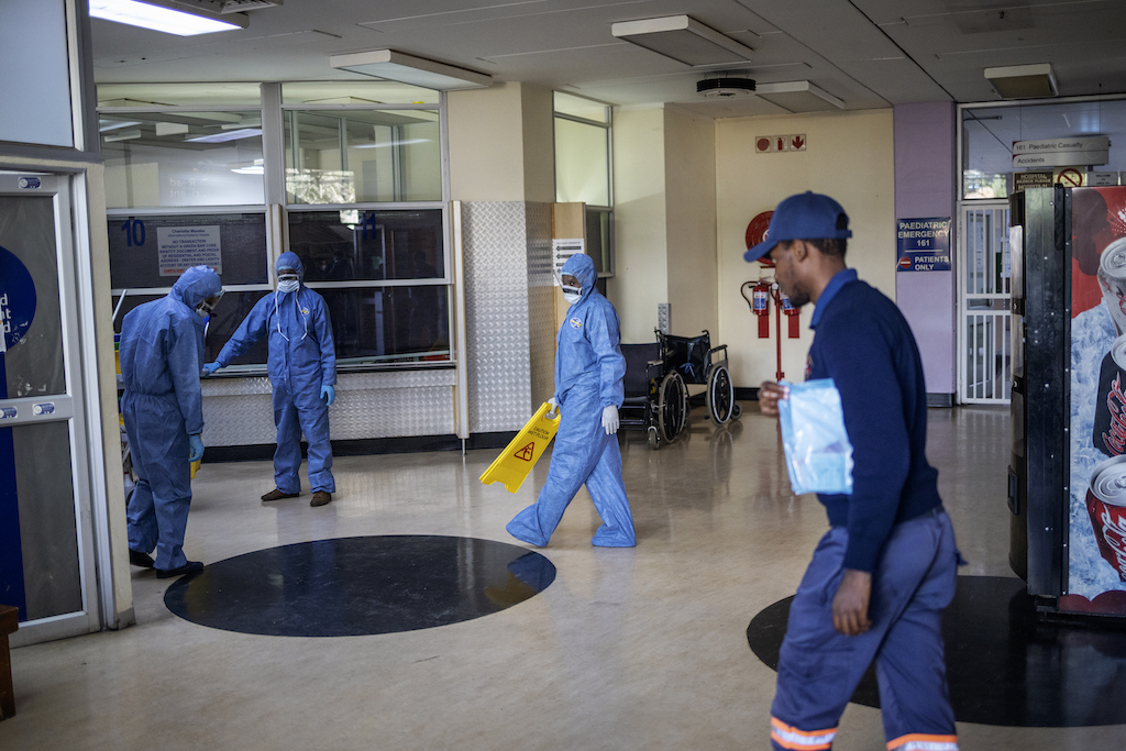 Workers wearing protective clothing clean an entrance hall of the Charlotte Maxeke Hospital in Johannesburg.