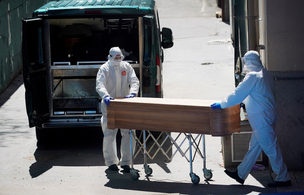 Mortuary workers push a coffin of a person who died at a nursing home during the coronavirus disease (COVID-19) outbreak in Leganes Madrid, near Madrid, Spain.