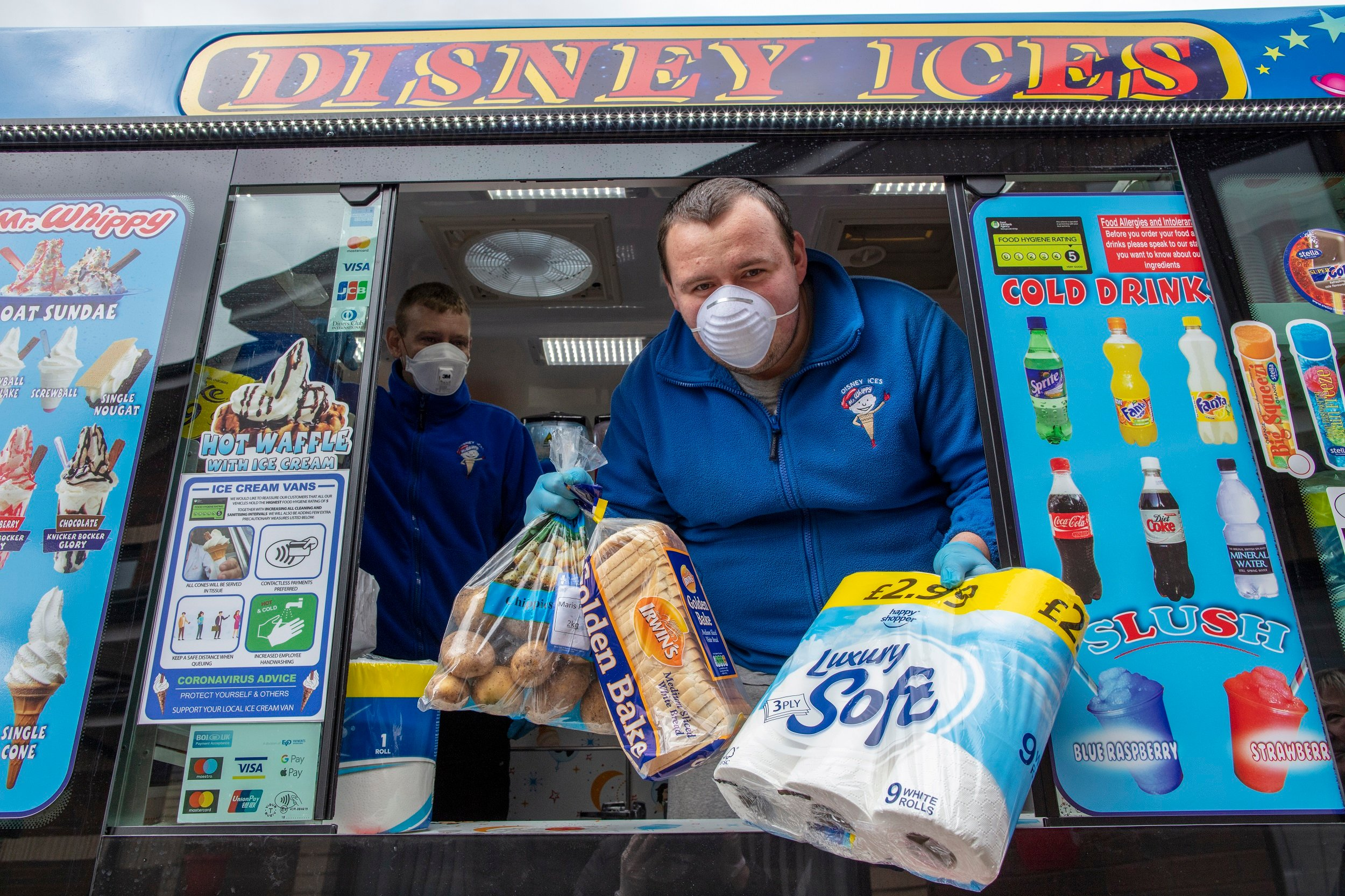 Workers sell food and household items from their ice cream van to local residents at a supported housing estate in west Belfast.