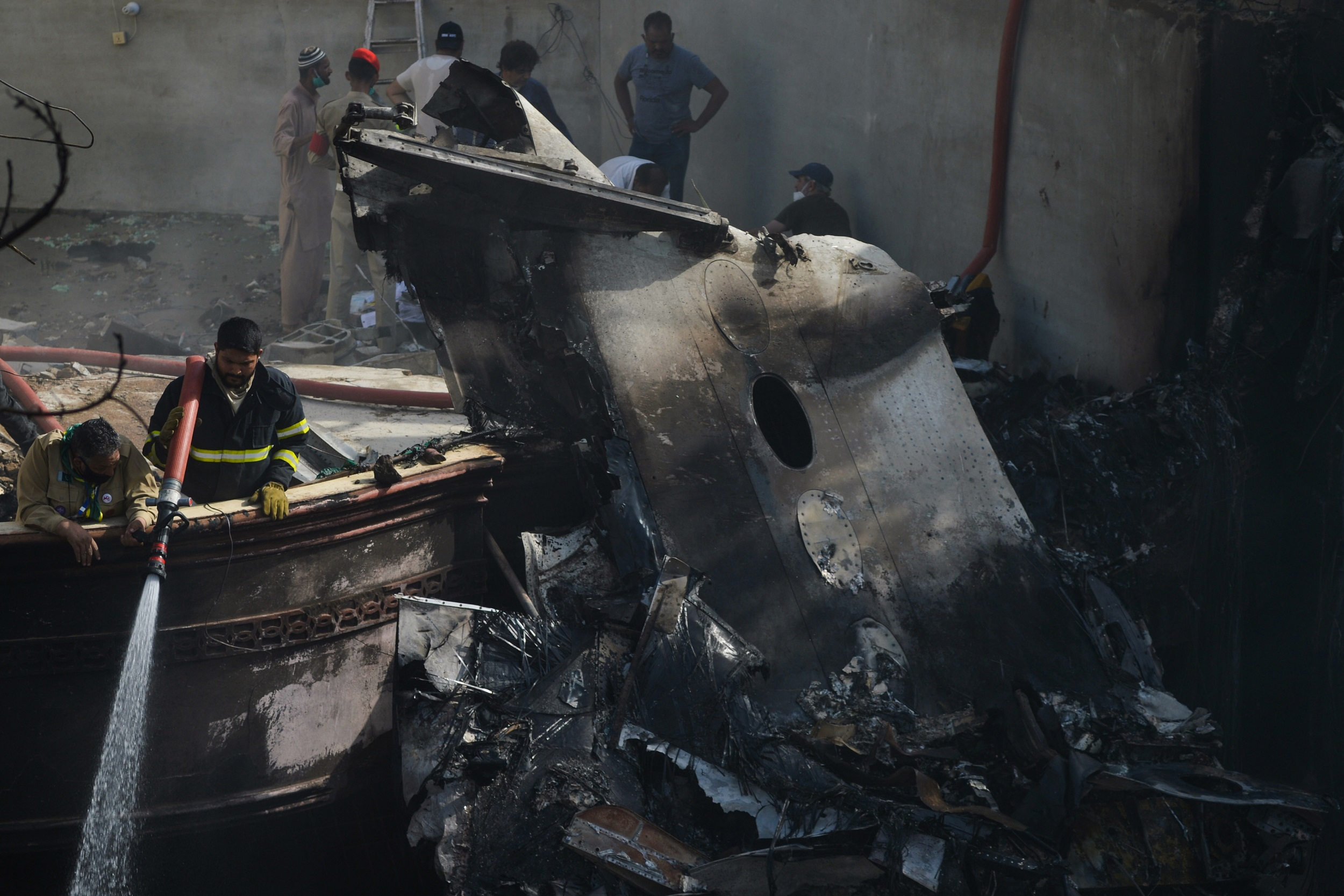 A firefighter sprays water on the wreckage of a Pakistan International Airlines aircraft after it crashed in a residential area in Karachi on Friday.