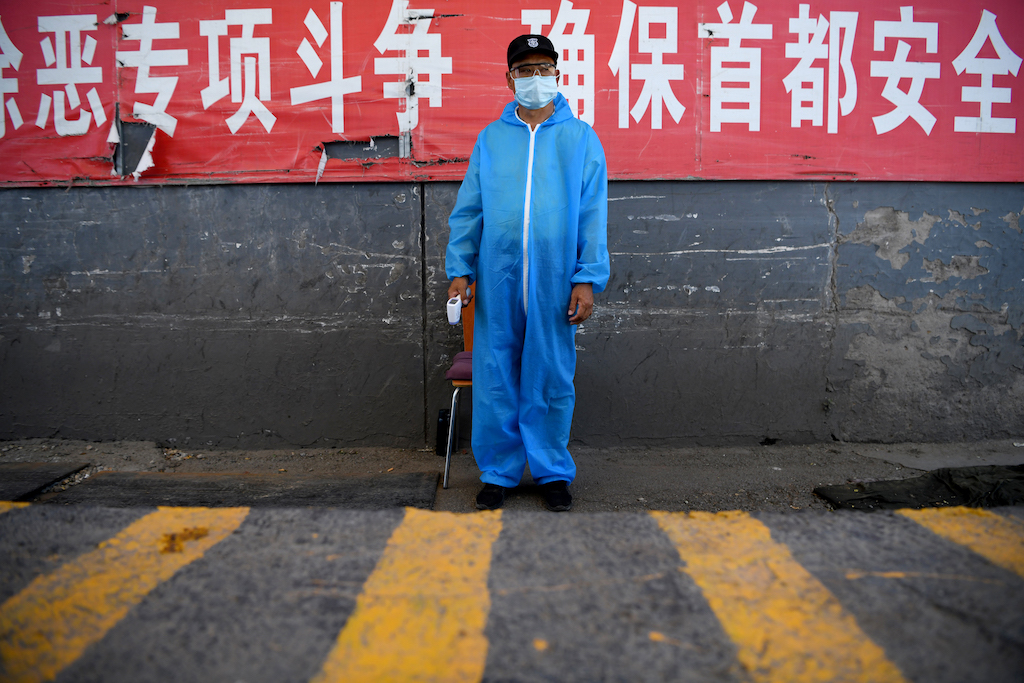 A security guard wearing a protective mask and suit stands at a checkpoint at the Xinfadi market in Beijing on June 14, 2020.
