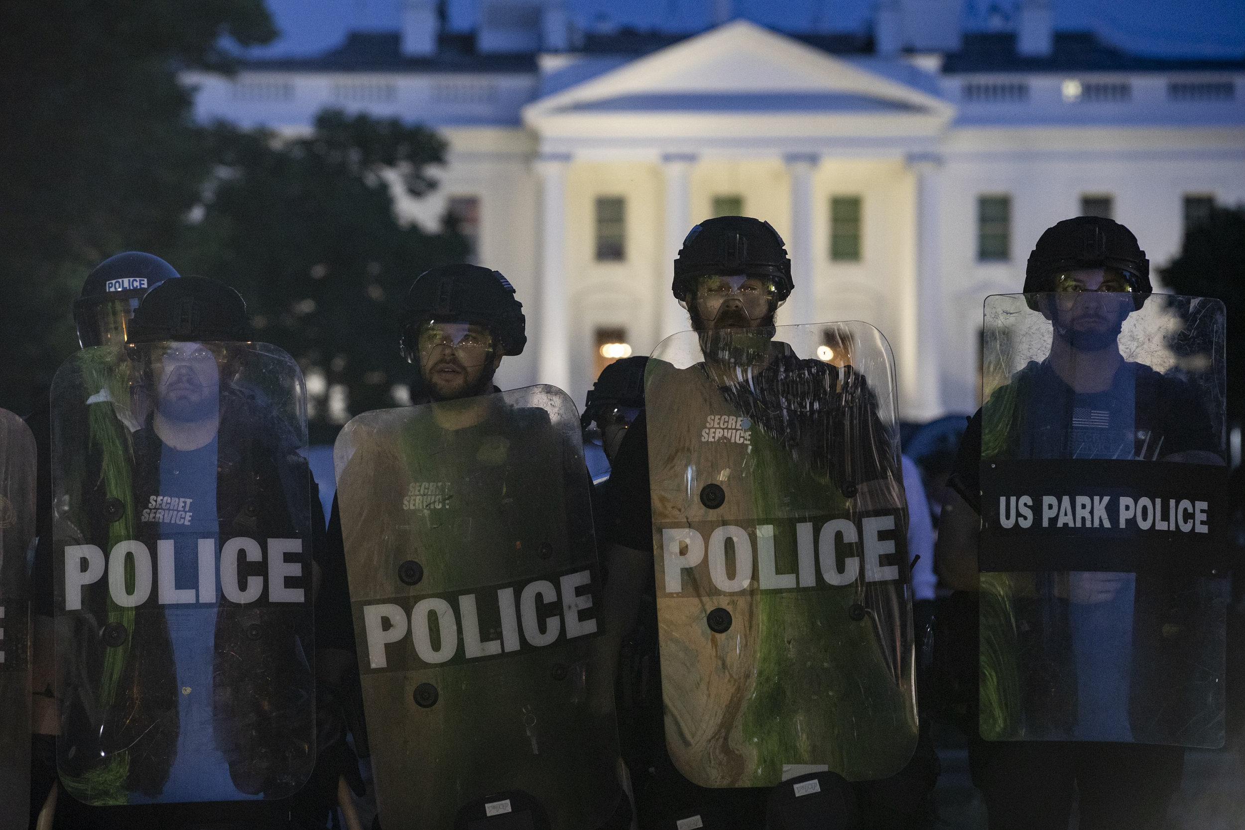 Police stand guard outside the White House as people gather to protest the death of George Floyd in Washington, DC.
