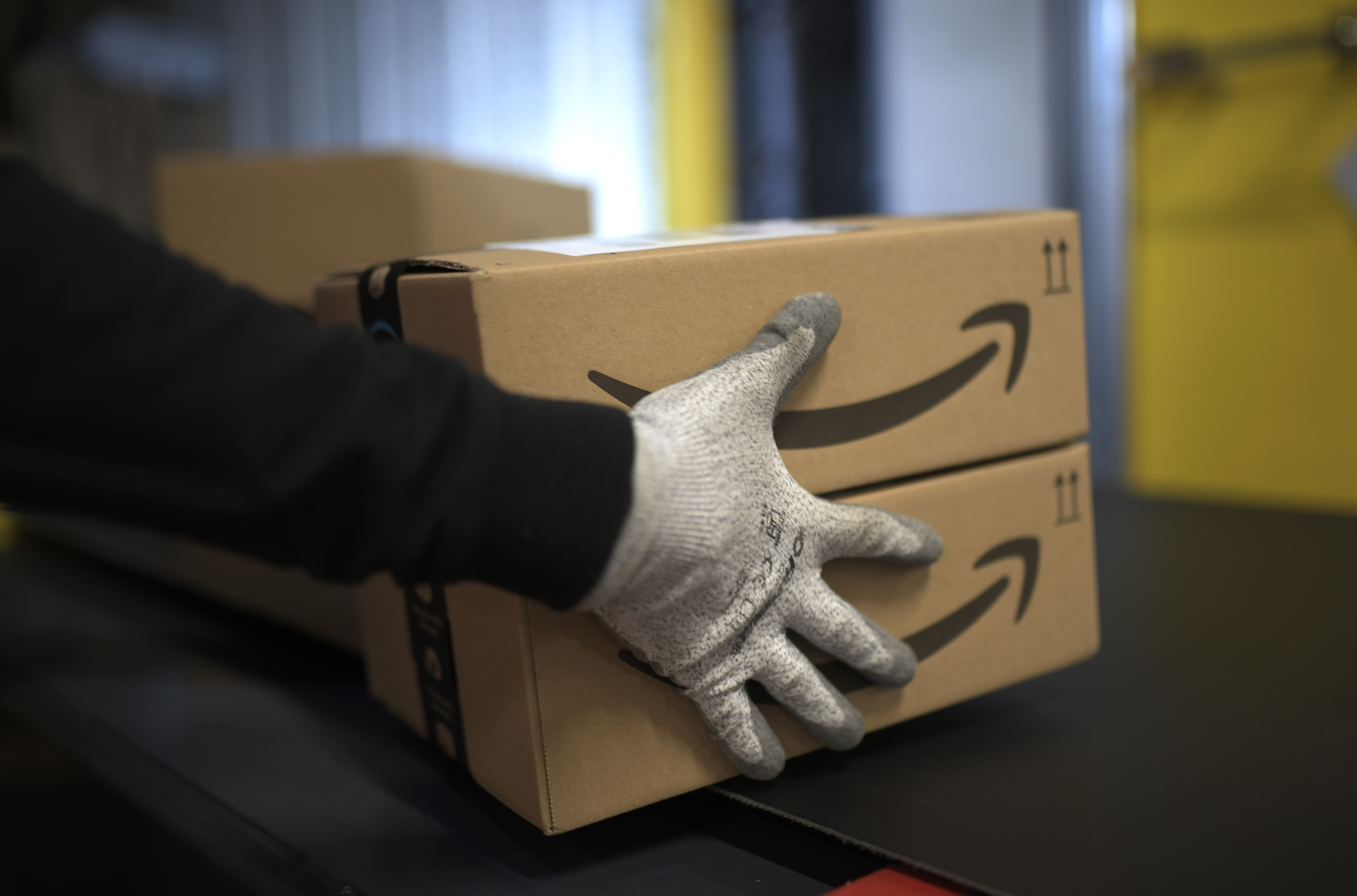 File: An employee carries a package at the distribution center of US online retail giant Amazon in Moenchengladbach, on December 17, 2019.