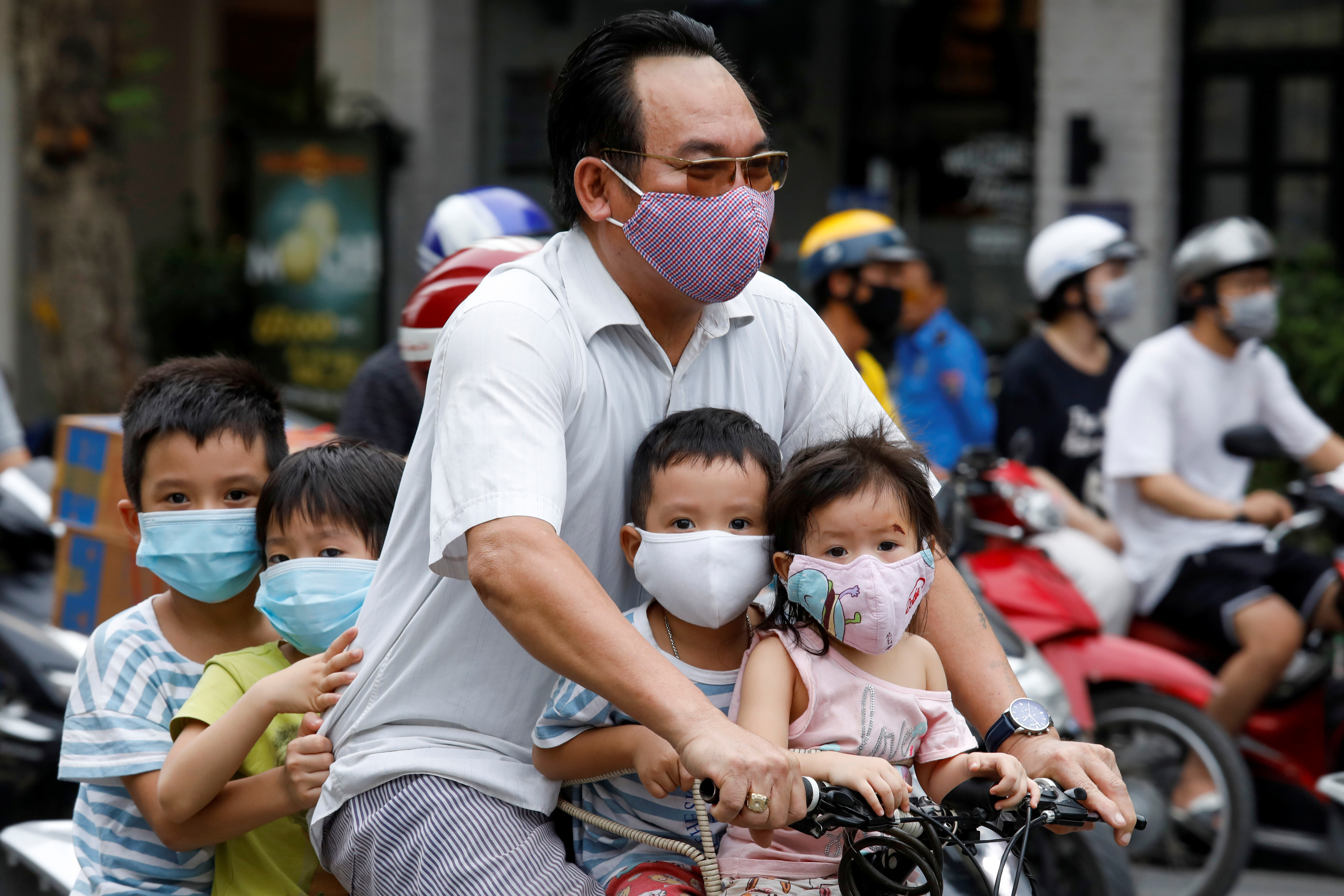 A man and his children, all wearing protective masks, ride a bicycle on a street during the coronavirus disease (COVID-19) outbreak, in Hanoi, Vietnam July 27, 2020.