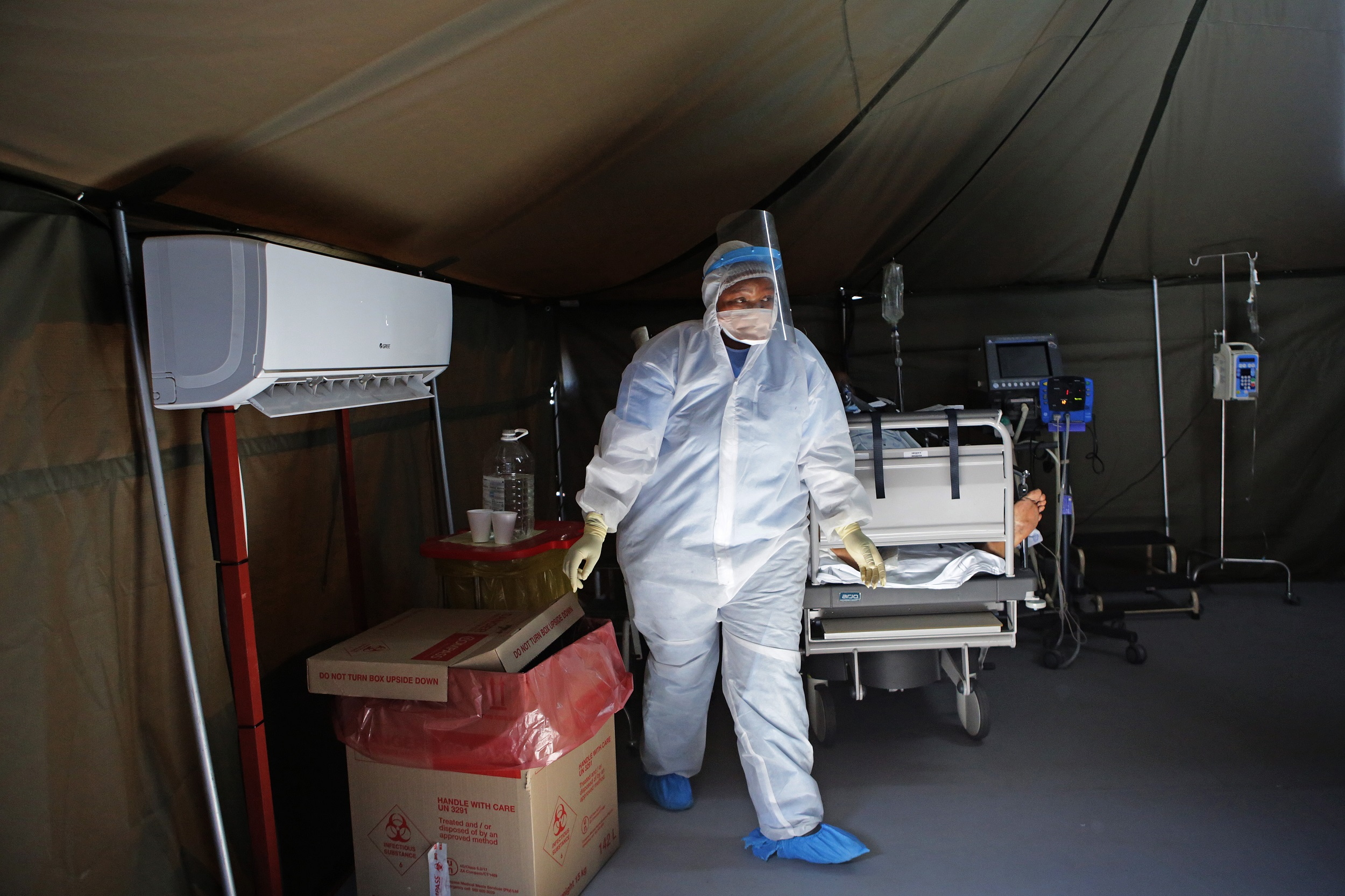 A healthcare worker wearing personal protective equipment (PPE) walks in a tent dedicated to the treatment of possible COVID-19 patients at the Tshwane District Hospital.
