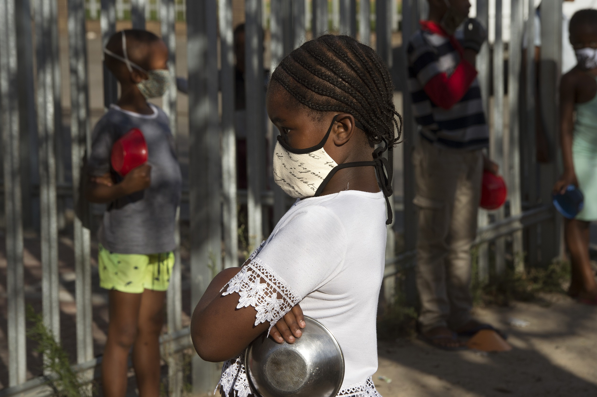 Children wait in lines at a crèche in Langa, near Cape Town to receive a meal which is part of a project to feed people made vulnerable under the lockdown.