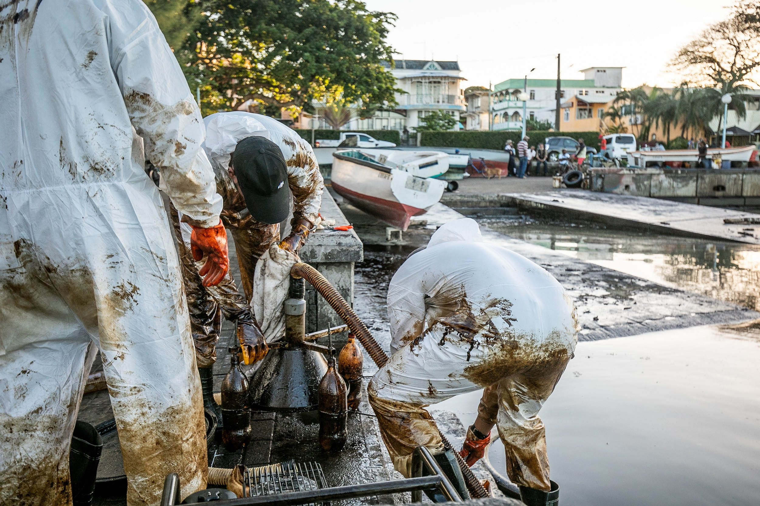 Fishermen and skippers tend to a makeshift oil extraction device at the Mahébourg waterfront in Mauritius in order to prevent a further oil spill from the MV Wakashio vessel.