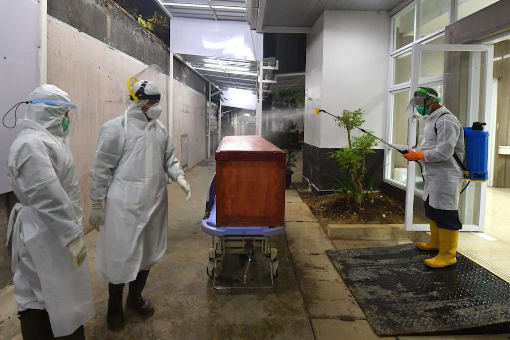 This picture taken on September 9, 2020 shows a hospital worker spraying disinfectant over a coffin bearing the body a patient who succumbed to the COVID-19 coronavirus, at the Bogor general hospital in Bogor, West Java.