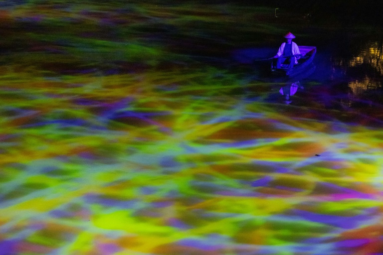 On the surface of a pond, abstract lines of violet, yellow and green light combine