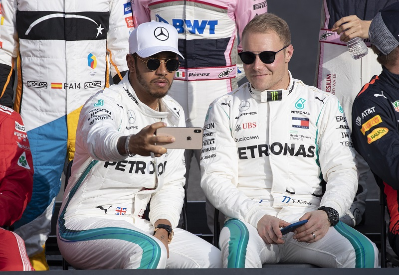British Formula One driver Lewis Hamilton of Mercedes AMG GP (L) and Finish Formula One driver Valtteri Bottas of Mercedes AMG GP (R) take a selfie as they pose for photographers on the track ahead of the Abu Dhabi Formula One Grand Prix