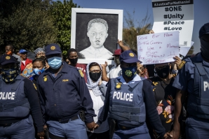 Community members hold a placard with an image of Nathaniel Julies during his funeral service in Eldorado Park, near Johannesburg.